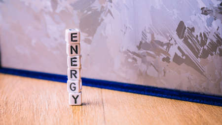 ENERGY cube letter in pile with solar silicon cell surface in background. Concept of renewable clean energy