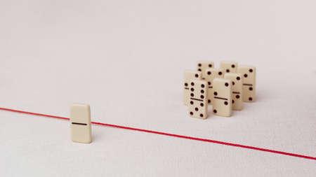 bulling: Expulsados ??del grupo, incapaz de cruzar la línea roja que los separa. Escena con el grupo de dominó. Concepto de acusación de culpabilidad persona, bulling o marginado en el equipo. fondo brillante Foto de archivo