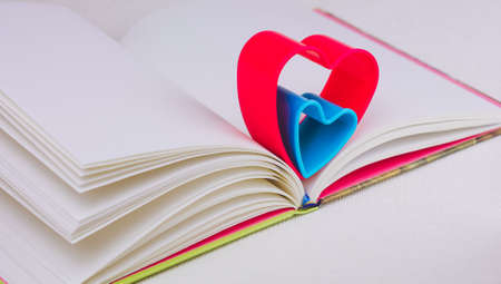 Red and blue hearts over diary book on white table