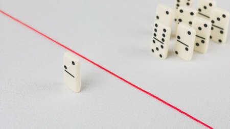 Vertrieben aus der Gruppe, nicht in der Lage, die rote Linie zu überqueren, die sie trennt. Szene mit Gruppe von Domino. Konzept der Anschuldigung schuldige Person, Bulling oder Outcast im Team. Heller Hintergrund