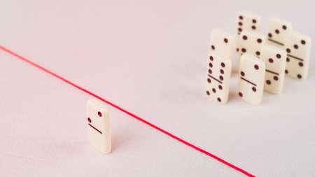 Expulsados ??del grupo, incapaz de cruzar la línea roja que los separa. Escena con el grupo de dominó. Concepto de acusación de culpabilidad persona, bulling o marginado en el equipo. Foto de archivo - 76057776