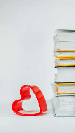 One heart shape lean on books pile placed on the white surface Stock Photo