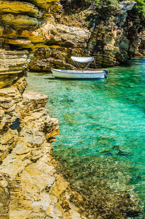 paleokastritsa: White boat in small cute azure bay surrounded by lime stone cliffs in Corfu island, Greece