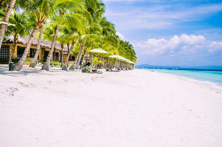 Tropical sandy beach at Panglao Bohol island with Sme Beach chairs under palm trees. Travel Vacation. Philippines Stok Fotoğraf