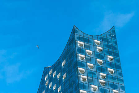 housing lot: Hamburg, Germany - May 28, 2017: Top shape of Elbphilharmonie with white windows and some white clouds in sky, Hamburg, Germany