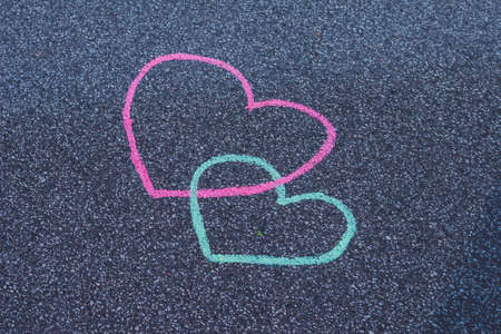 Two hearts drawing chalk on the asphalt.