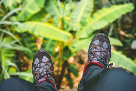 Hanging feet with trakking footwear after long hike from the mountains on Santo Antao Island, Cape Verde. Banana leaves underneath. Stock Photo
