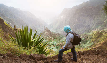 Traveler with backpack looking over the rural landscape with mountain peaks and ravine in dust air on the path from Xo-Xo Valley. Santo Antao Island, Cape Verde Stock Photo