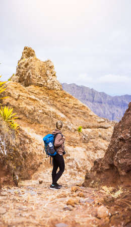 Woman hiker on the stony trekking trail in front of the barren mountain peak on Santo Antao island, Cabo Verde