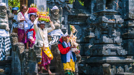GOA LAWAH, BALI, INDONESIA - November 3, 2016: Balinese people in traditional clothes carry bless gift after ceremony at Pura Goa Lawah temple, Bali, Indonesia