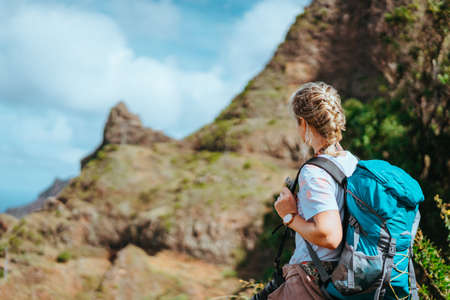 Woman with camera and backpack in front of the arid fins of rocks on Santo Antao island, Cabo Verde