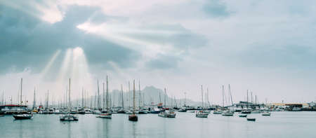 Sailboats and pleasure boats in the porto grande bay of the historic city Mindelo. Sunrays Stock Photo