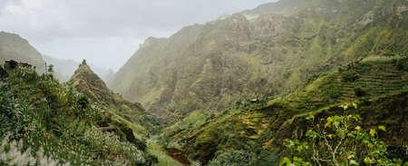 Trekking route to the Xo-Xo Valley. Harsh peaks and immense mountain walls around the ravine. Local dwellings built on the mountain ridge. Santo Antao island, Cape Verde Stock Photo