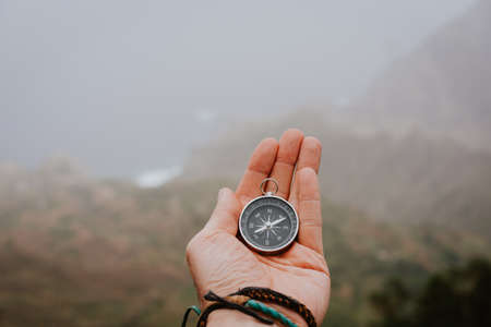 Looking at the compass to figure out right direction. Foggy valley and mountains in background. Santo Antao. Cape Cabo Verde Imagens