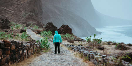 Male hiker admiring beautiful dramatic landscape of rugged coastline on the trekking trail to Cruzinha. Santo Antao Cape Verde