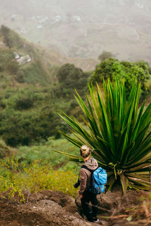 Woman with camera and backpack near one huge agave plant with arid landscape of location called Corda in background. Santo Antao island, Cabo Verde