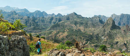Man hiker walking among remote mountainous landscape with agriculture terraces in vertical valley sides. Santo Antao Island, Cape Verde Stock Photo