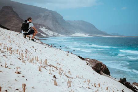 Photographer with camera enjoying quaint moment in scenic coastal landscape of sand dunes and volcanic cliffs. Baia Das Gatas, near Calhau, Sao Vicente Island Cape Verde Фото со стока