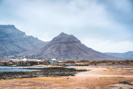 Mysterious landscape of sandy coastline with fisher village and black volcanic mountains in background. Baia Das Gatas. North of Calhau, Sao Vicente Island Cape Verde Stock Photo