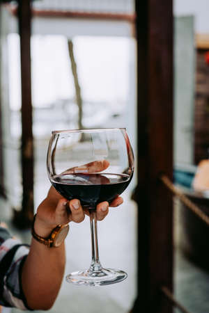 Woman hand holding a wine glass with red wine