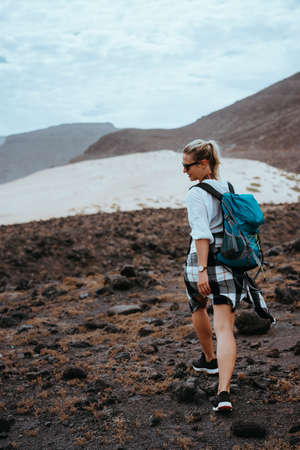 Woman hiker walking on barren rocky terrain among black volcanic boulders and white sand dunes. Sao Vicente Cape Verde Stock Photo