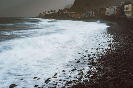 Rough ocean waves with blowing spray rolling onto the rocky volcanic shore. Ribeira Grande Village Stock Photo