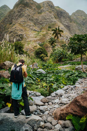 Male photographer in verdant valley covered with lotus plants. Santo Antao Cape Verde Stock Photo