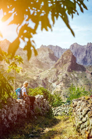 Girl resting on the hiking trail leading through arid rocky terrain towards Coculli village on Santo Antao Cape Verde