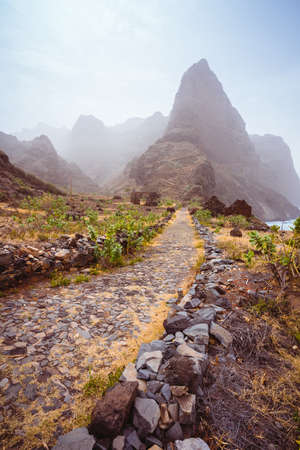 Cobbled hiking path to Ponta do Sol over amazing arid Aranhas valley with huge mountain peak and house ruins. Santo Antao Island, Cape Verde Stock fotó