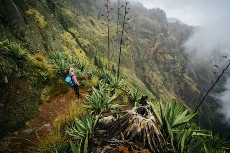 Female traveler staying on the cove volcano edge above the foggy green valley overgrown with agaves Santo Antao island in Cabo Verde Stock Photo