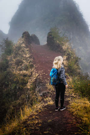 Woman hiker with backpack on the narrow misty path of mountain ridge on Santo Antao island, Cape Verde Stock fotó