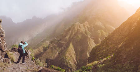 Man in high altitude rocky making picture of mountain landscape in front of a deep ravine. Warm sun light filled the valley. Trekking trail on Santo Antao Cape Verde