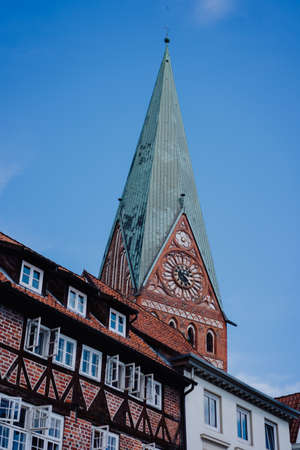 Tower of the St. Johannis church of Luneburg and an old half-timbered red bricks house in front. Germany Stock Photo