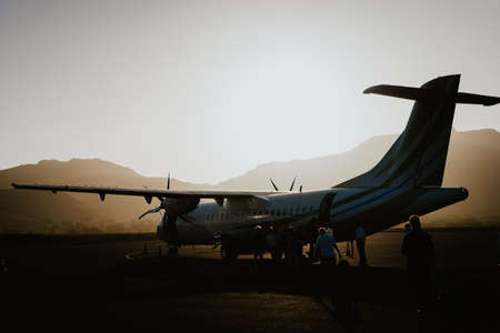 Passengers boarding to propeller aircraft on dusty morning. Mountain range surrounding runway on Sao Vicente airport Cape Verde