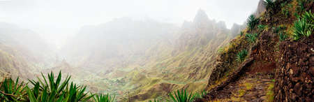 Panorama of Xo-Xo valley surrounded by harsh mountain peaks. Steep walk path covered by yucca plants lead down to Ribeira Grande. Santo Antao island, Cape Verde