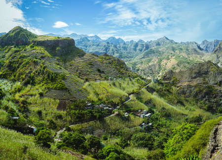 Cape Verde. Gorgeous panoramic view of famous fertile Paul Valley. Agriculture terraces of sugarcane in vertical valley sides, people dwellings, rugged peaks and motion clouds on horizon Stok Fotoğraf