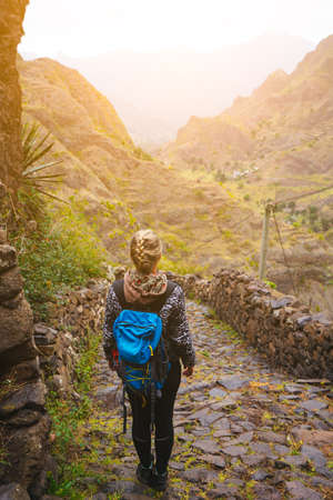 Female hiker with blue backpack staying on the stony cobbled trekking trail leading down to the valley between barren mountain peak on Santo Antao island, Cabo Verde Stock Photo
