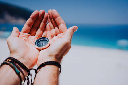 Open hand palms with metal compass on the sandy beach. Searching your way concept. Blue sea in background. Point of view pov Stock Photo