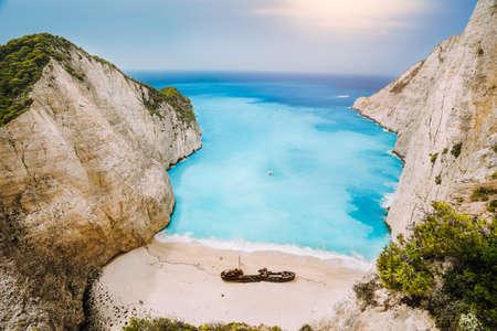 Shipwreck on Navagio beach. Azure turquoise sea water and paradise sandy beach in evening light. Famous tourist visiting landmark on Zakynthos island, Greece