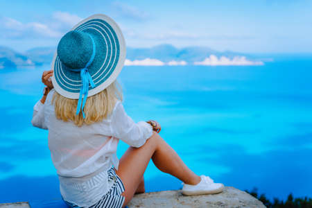 Attractive female tourist with turquoise sun hat enjoying amazing azure seascape, Greece. Cloudscape shadows on the sea surface in background Stock Photo