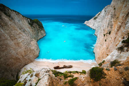 Shipwreck in Navagio beach. Azure turquoise sea water and paradise sandy beach. Famous tourist visiting landmark on Zakynthos island, Greece. Stock Photo