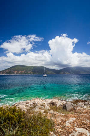 Fiskardo town, crystal clear transparent blue turquoise teal Mediterranean sea water. White yacht in open sea at anchor under amazing white clouds, Kefalonia, Ionian islands, Greece.