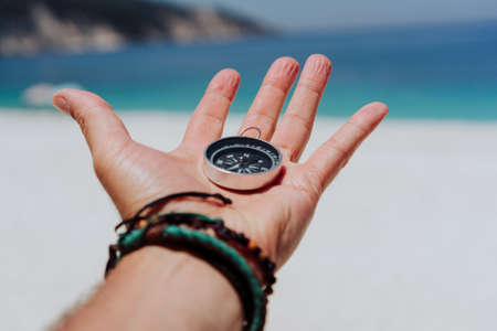 Outstretched hand holding black metal compass against white sandy beach and blue sea. Find your way or goal concept. Point of view pov Stok Fotoğraf
