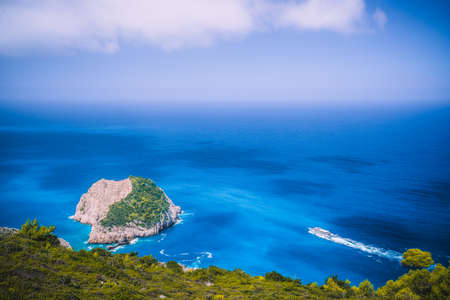 Zakynthos fantastic west coastal view with white cliff. White tourist ship sailing full speed on open azure sea water under beautiful cloudscape Stock Photo