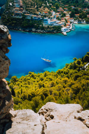 Epic view to blue bay of Assos village Kefalonia from Fortress above. White yacht at anchor in calm beautiful colored lagoon water surrounded by pine and cypress trees. Greece Stock Photo