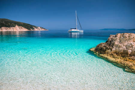 Beautiful azure blue lagoon with sailing catamaran yacht boat at anchor. Pure white pebble beach, some rocks in the sea Standard-Bild