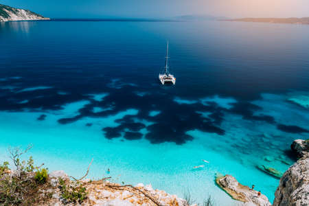 Weiße Katamaran-Yacht vor Anker in ruhiger klarer azurblauer Wasserlagune. Nicht erkennbare Touristen entspannen und entspannen sich am versteckten Strand