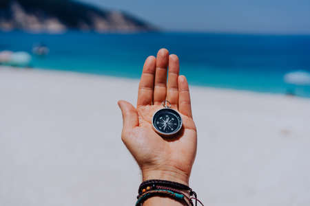 One open stretched hand palm with black metal compass on the sandy beach. Find your wish goal way concept. Blue sea in background. Point of view pov 写真素材
