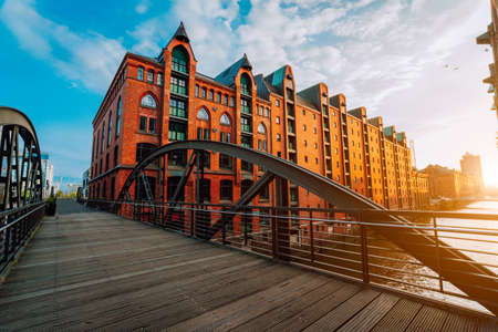 Pedestrian arch bridge over canals in the Speicherstadt of Hamburg. Warm golden hour sunset light on red bricks buildings 免版税图像