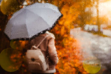 Beautiful golden autumn season. Watercolor like blurred blond girl with backpack and bright umbrella stands under rainy drops and droplets. Backlit sunset sun beam flares on sccreen. Wet weather